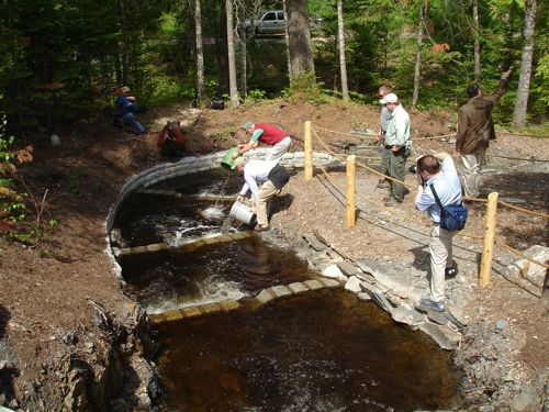 Working on the fishway at Leonards Mills Logging Museum Dam. Credit: Maine Forest and Logging Musem