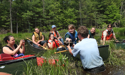The students look at a snapping turtle found while releasing the Blanding's turtles. Credit: Keith Shannon/USFWS