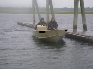A woman drives a small motorboat along a dock with a man passenger.