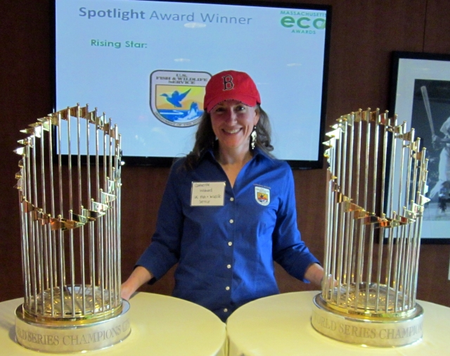 A woman in a blue shirt and and red hat stands bewteen two world series trophies