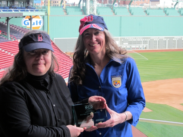 Two women wearing Red Sox hats hold a glass award with the Green Monster in the background