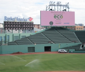 A big screen behind a green ballfield