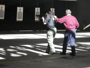 A woman shoots a rifle at some targets while a man stands behind her with his hand on her shoulder. Both wear ear muffs.