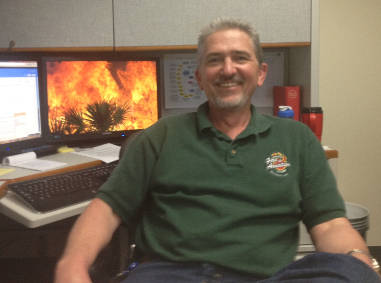 A man in a green shirt sits in front of a computer with flames in the background