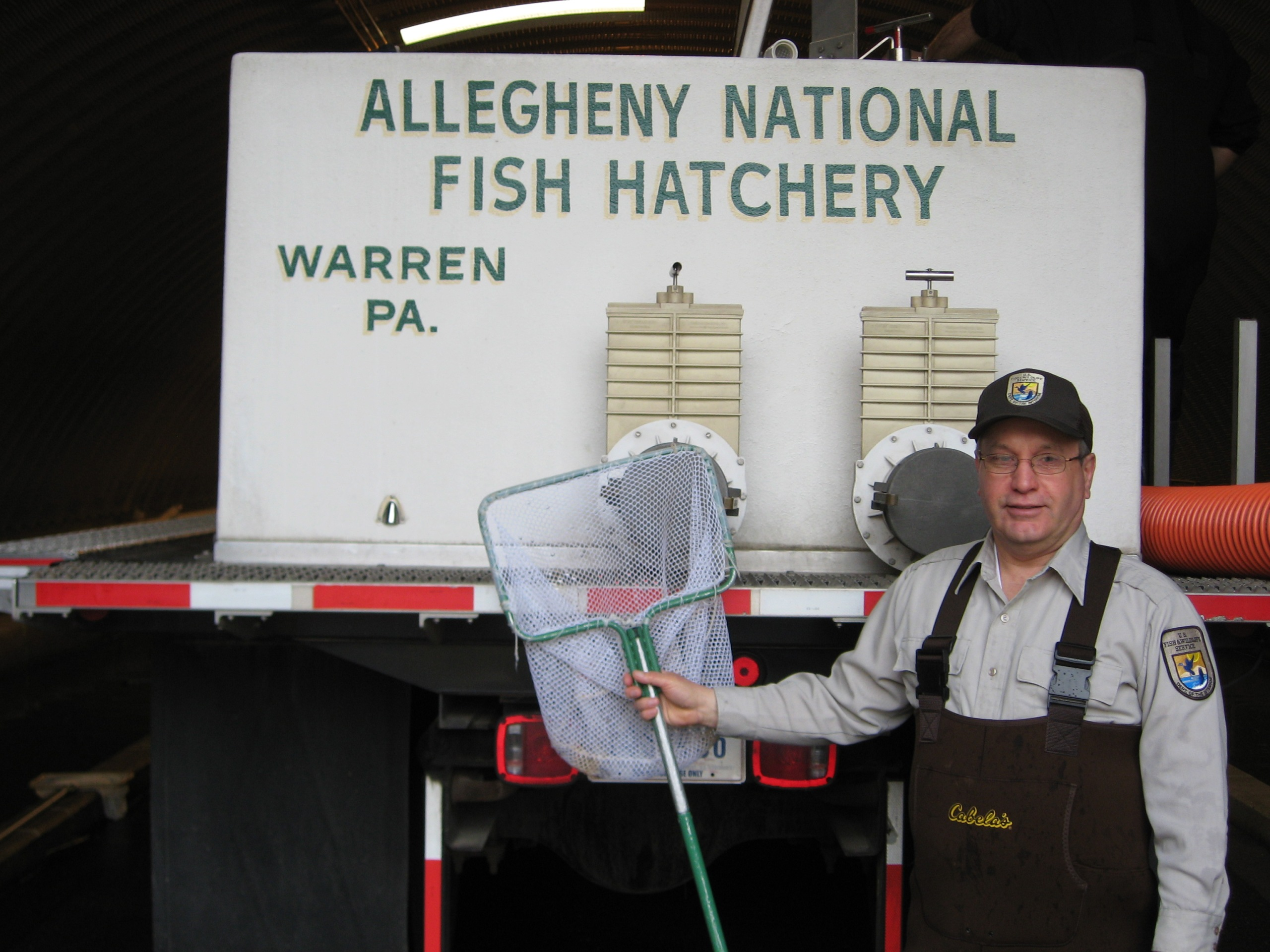 A man stands with waders and a net in front of an Allegheny National Fish Hatchery fish truck