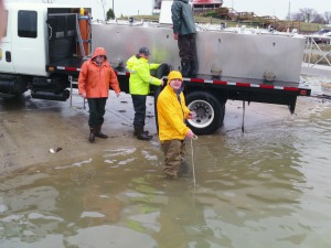 a man in a yellow jacket and waders stands in water with a hose coming off a truck