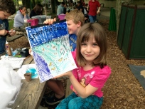 "Allegra Breitkopf holds up her colored ""Share the Beach"" with shorebirds activity book. Credit: USFWS"
