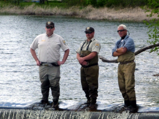 Three men in waders stand on a small spillway before water