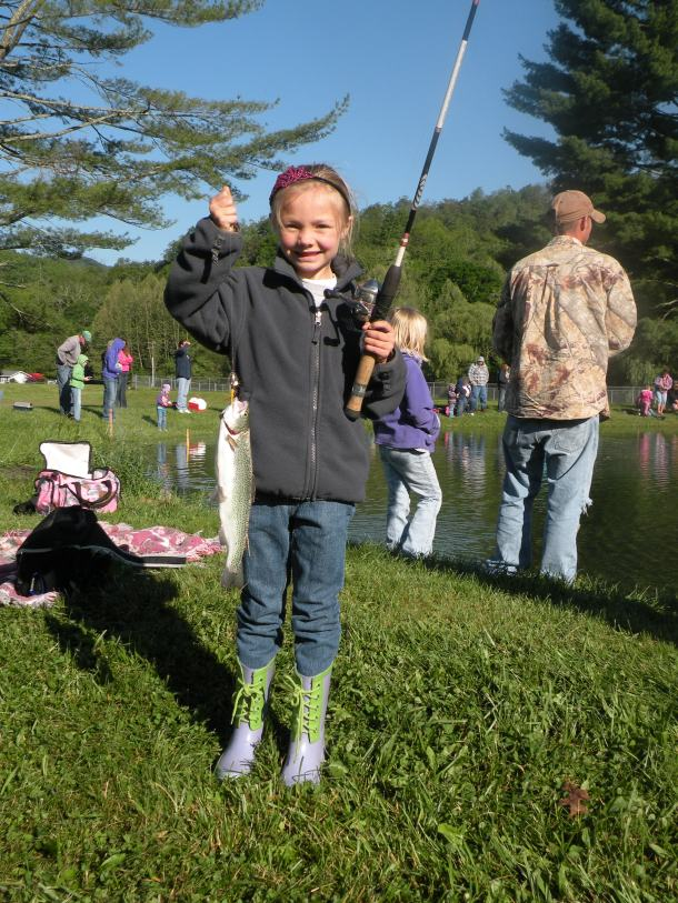 A girl holds a fishing pole and the fish she caught.