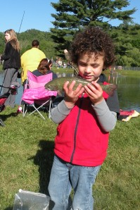 A child in a red shirt and dark curly hair and skin holds a fish.