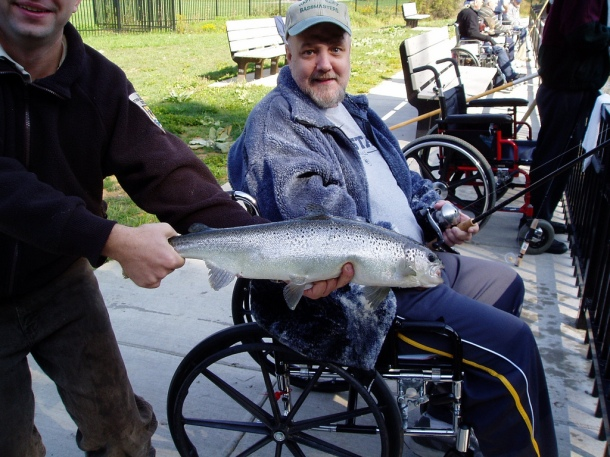 A man in a wheelchair displays a fish he caught