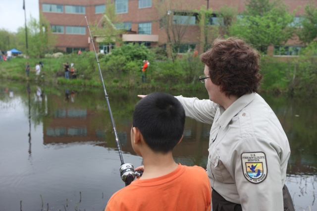 Tracy Copeland of the U.S. Fish and Wildlife Service mentors a young fisherman. Credit: USFWS