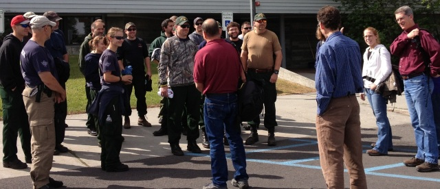 A group of people stand in a parking lot.