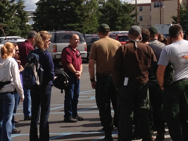 A group of people stands out in a parking lot.