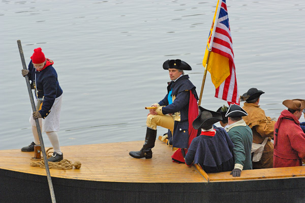 Men dressed in colonial wear in a boat with an American flag