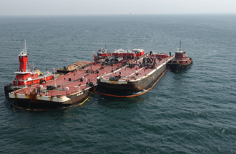 A large barge is being offloaded next to a tugboat in the ocean.