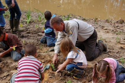 Biologist Rich Mason helps students plant a schoolyard wetland. Credit: Laurie Hewitt/USFWS