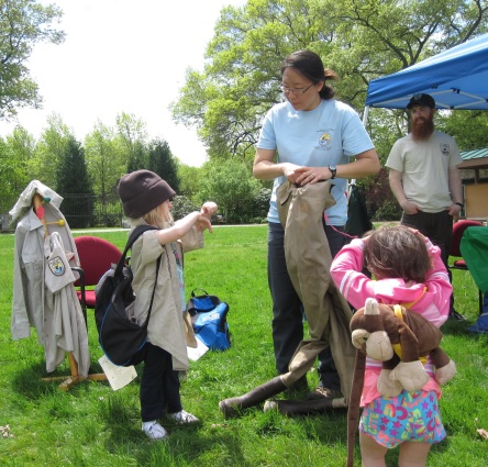 Juhyun Kim, Antioch graduate student interning with Eastern Massachusetts refuge, helps kids dress up in Fish and Wildlife gear. Credit: USFWS