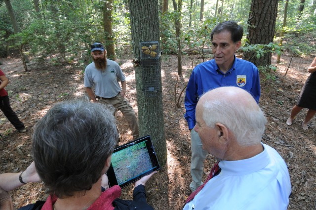 Secretary Sally Jewell, Senator Ben Cardin and Director Dan Ashe review photos of Delmarva fox squirrels captured by a trail camera on Blackwater National Wildlife Refuge. Trail cameras are one of the methods that has been used to monitor the species over the years. Photo from DOI.