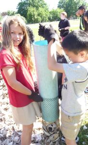 4th grade students from D'Ippolito Elementary School lift their full shell tube up to complete their shell bag.