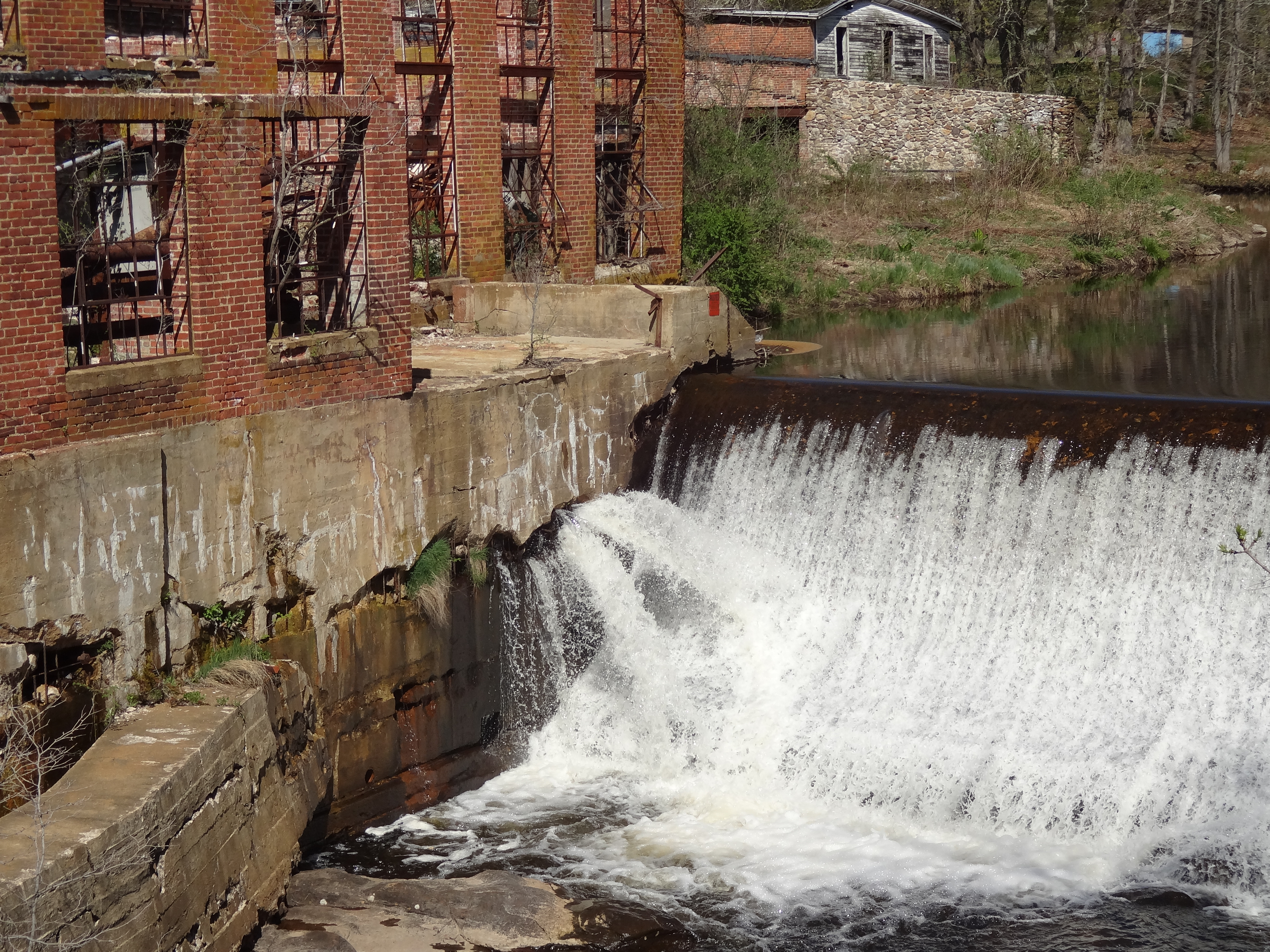 Water surges from huge gaps in the cracking base of the Norton Paper Mill in Colchester, Conn. Once the paper mill, dam and empty mill house (in the far distance) are removed -  visitors will enjoy access to a newly established, town-owned public park. Credit: Lia McLaughlin/USFWS