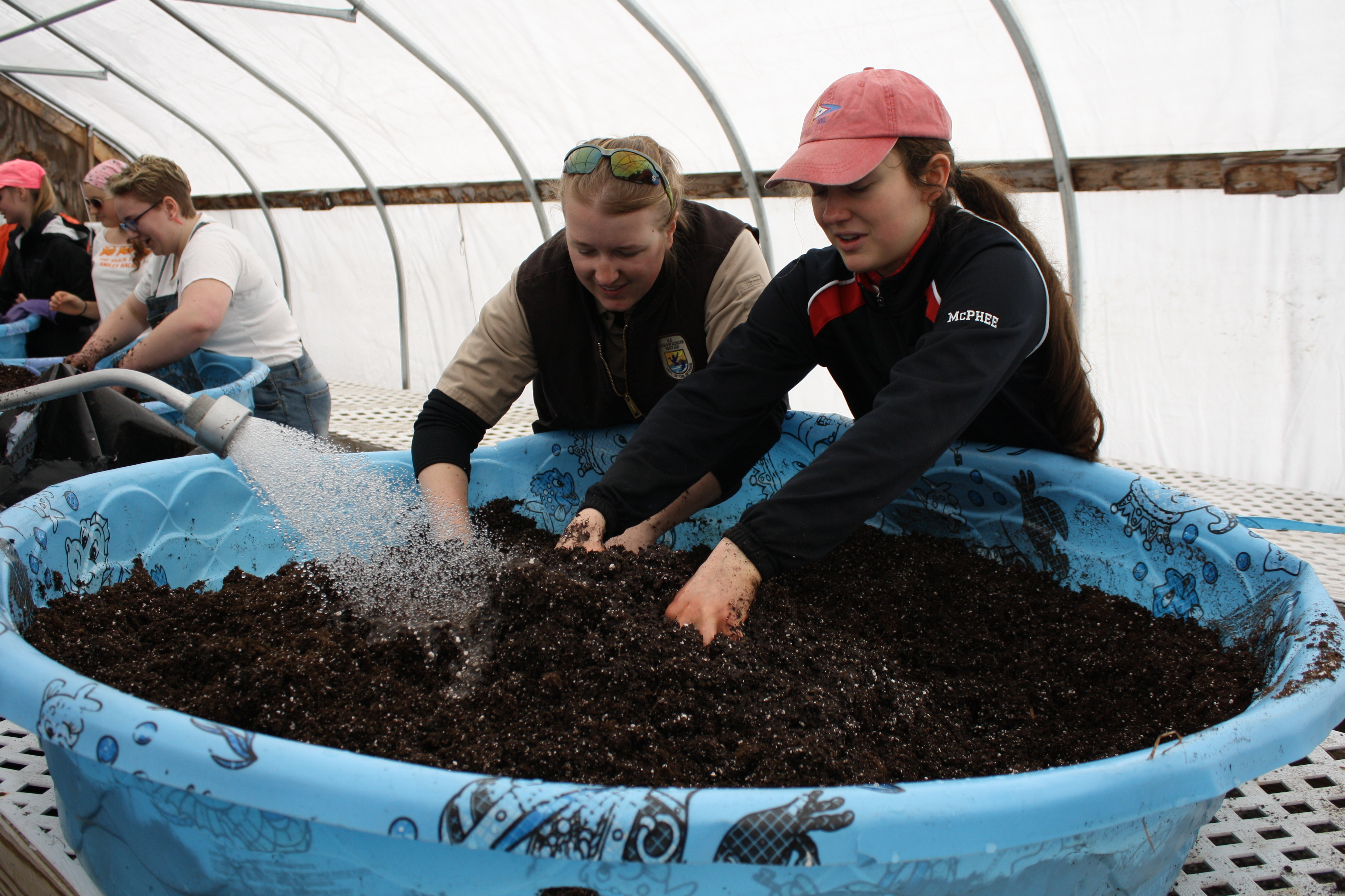Megan Zopfi, biological sciences technician at U.S. Fish and Wildlife Service, gets her hands dirty as she prepares soil for plants with a Coastal Studies for Girls team member.