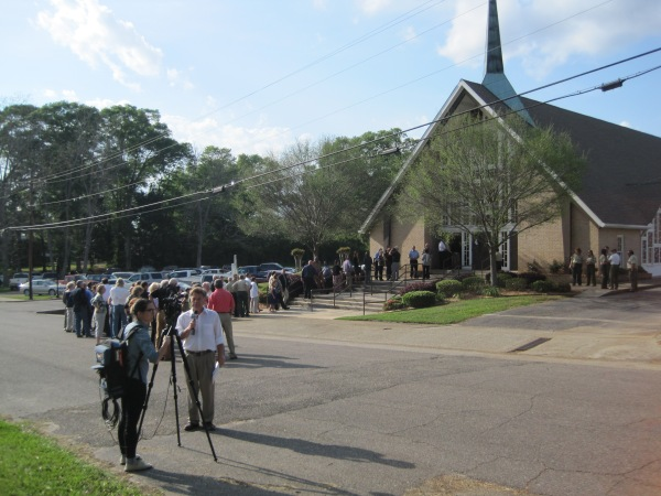 A church with a long line of people coming out of it with a reporter and camera in the foreground.