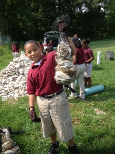 A student at West Avenue School proudly shows off a shell bag built for the Gandy's Beach oyster reef. Credit: Project PORTS staff