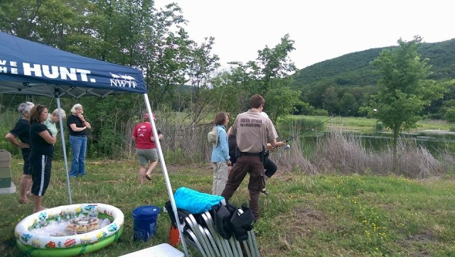 Federal wildlife officer, Mike McMenamin, introduces the ladies to casting by practicing with a bobber on land. Photo credit: NWTF