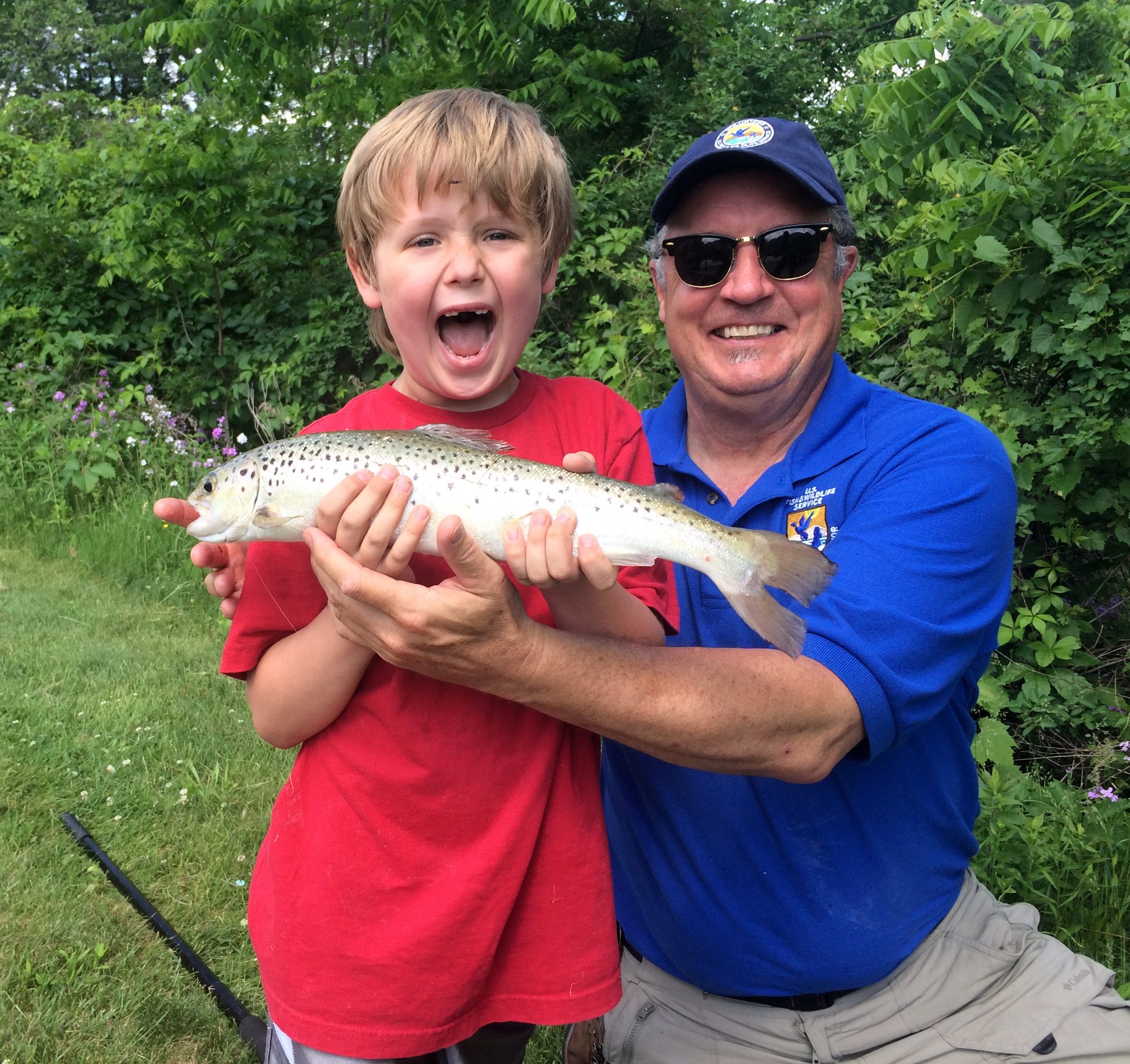 An excited young angler shows off his prize catch with Dr. Mike Millard at the Northeast Fishery Center Kid's Fishing Day. Photo credit:USFWS