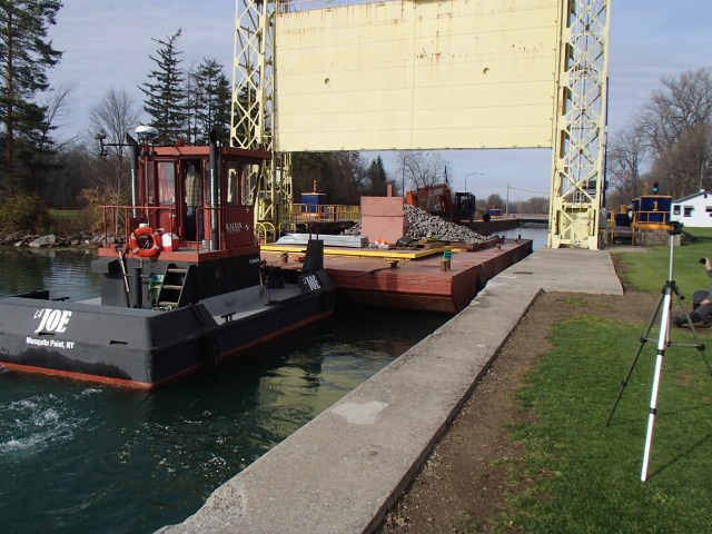 A tug boat pushes a barge loaded with rock through the lock. Photo credit: USFWS