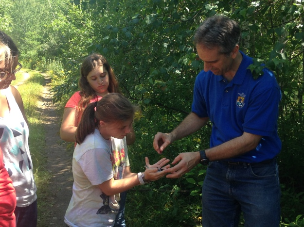 Dr. Randy Dettmers, wildlife biologist at U.S. Fish and Wildlife Service, places a black-capped chickadee ready for release into the gentle hands of a curious high school student from Flying Cloud Institute's Young Women in Science program.