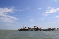Fog Point living shoreline - rock breakwater excavators on a barge. Credit: Lia McLaughlin/USFWS