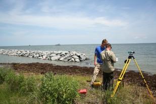 Staff surveying elevations during living shorline construction. Credit: Matt Whitbeck/USFWS