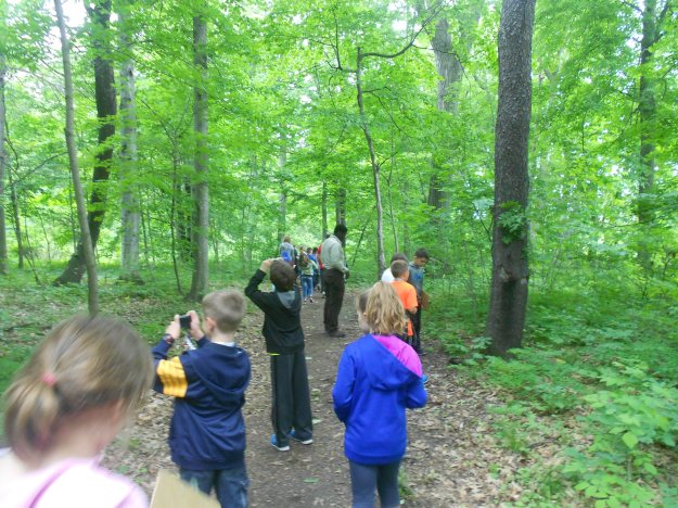 Elementary schoolchildren from northern Buffalo area enjoy a day in the woods, exploring nature through the lens of photography. Pathways Intern and Biologist, Kwamina Otseidu leads the group.