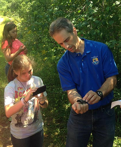 Randy Dettmers shares a bird caught during a mist netting demonstration at Silvio Conte National Wildlife Refuge with a local high school student .
