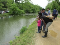 Little girl fishing with family and a Veteran that volunteered his time to help teach people fish.