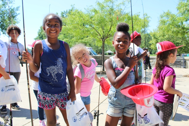 "These happy young anglers are all smiles as they receive their new fishing poles and other ""goodies"" provided to participants at the event. Photo credit: USFWS"