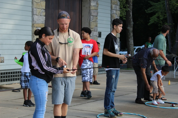 Staff from Connecticut's Dept. of Energy and Environmental Protection CARE program instruct youth on how to properly coast with the fishing poles.