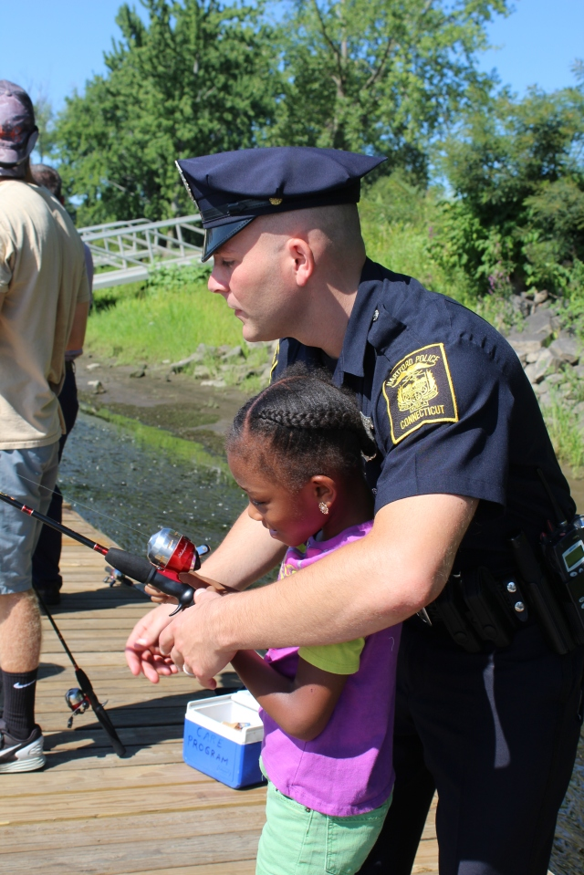 A Hartford city officer helps and enthusiastic young angler as she casts her pole into the river. Photo credit: USFWS