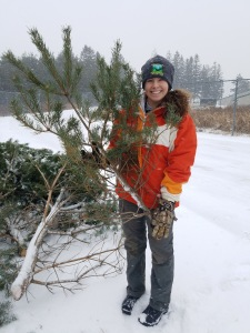 """AmeriCorps intern Mallory Gyovai showing off a """"Charlie Brown"""" Christmas Tree/Credit Lauren Merrill"""