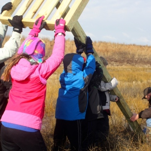 Biologists and volunteers raise an osprey nest platform at Poplar Island