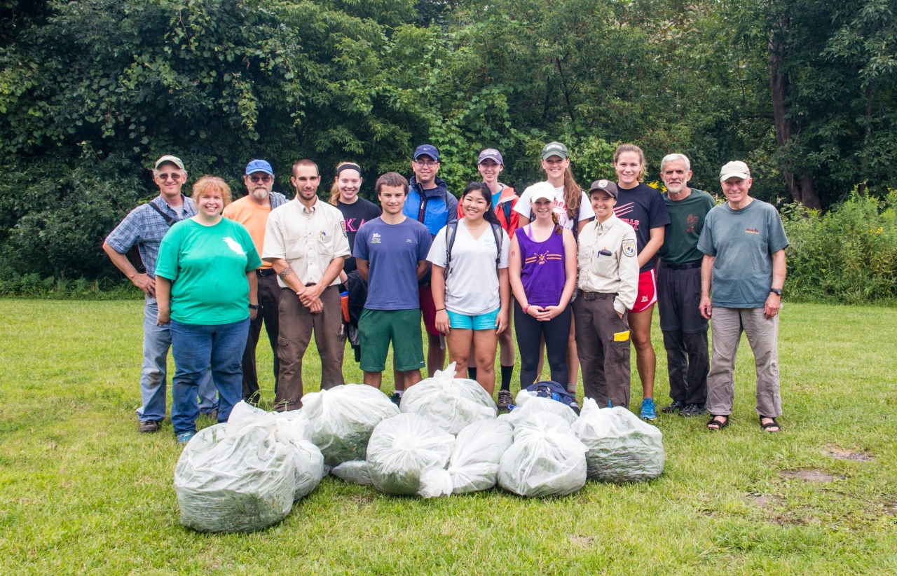 volunteers pose with trash bags of invasive plants