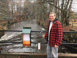 Burt Bacheller stands next to the observation box which houses the herring count logs. Credit: Jane Cairns
