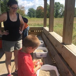 Visitors admiring an uncovered replica Native American tool. Photo Credit: Zintkala