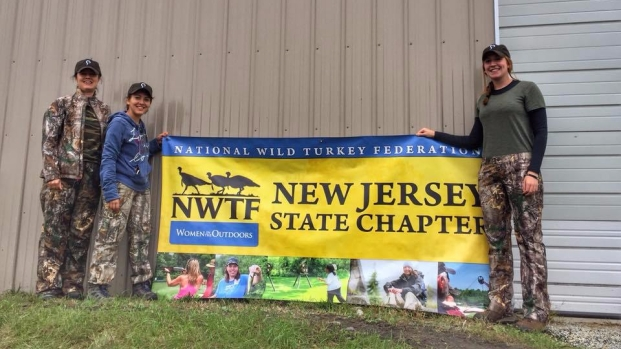Mikalia, Maria, and Tanya pose with National Wild Turkey Federation banner
