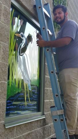 Patuxent intern Abraham Lopez painting staff window