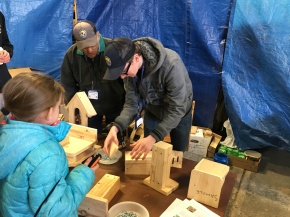Volunteer Carl Zenger, teaches new volunteer, the art of making feeding and nesting platforms for birds